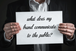 """man holding sign that says, """"what does my brand communicate to the public?"""""""