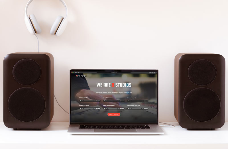 music studio website on laptop in between two speakers and headphones