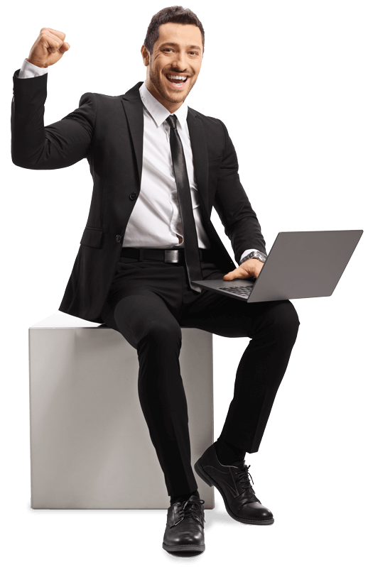 business professional in a suit sitting down with a laptop in lap fist pumping