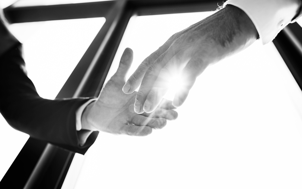 two people shaking hands in the sunlight