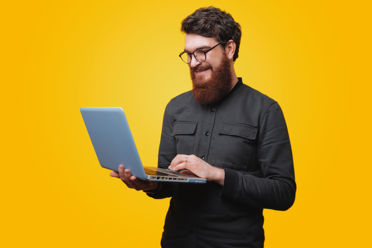 man smiling looking at laptop in front of yellow background