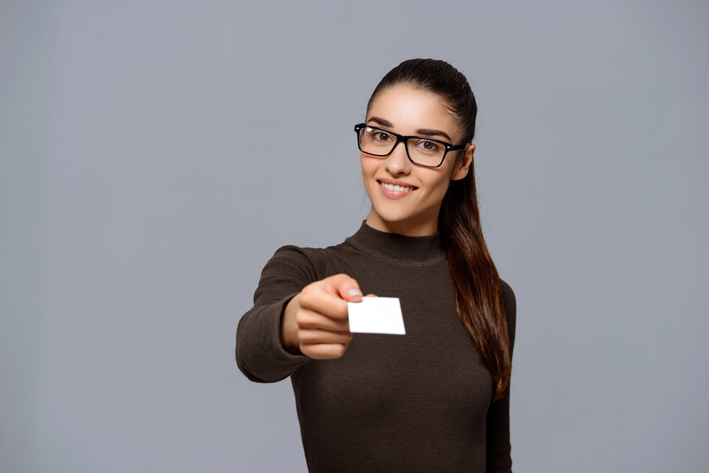 woman with glasses holding out business card
