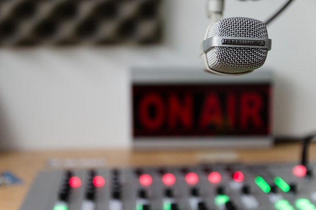 """on air"" sign behind a studio mixing console and condenser microphone"