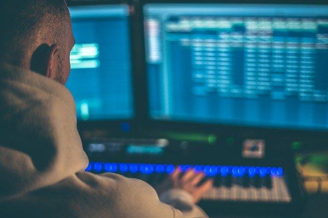 audio engineer editing tracks in digital audio workstation (DAW)