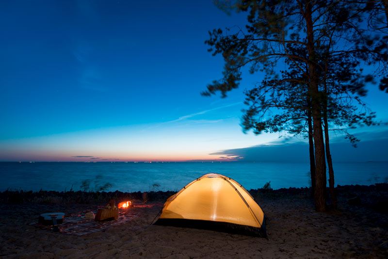 lit up tent on Lake Superior shoreline as sun sets on water