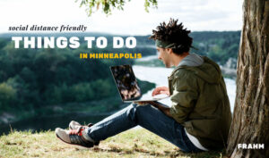 Man with laptop sitting atop bluff of Mississippi River - Social Distance Friendly Things to Do in Minneapolis title overlay