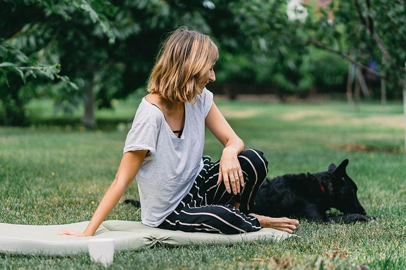 woman sitting on picnic blanket with dog nearby