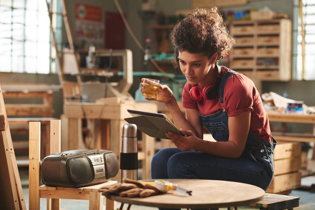 woman taking a crafting course on an iPad sitting in a woodworking shop