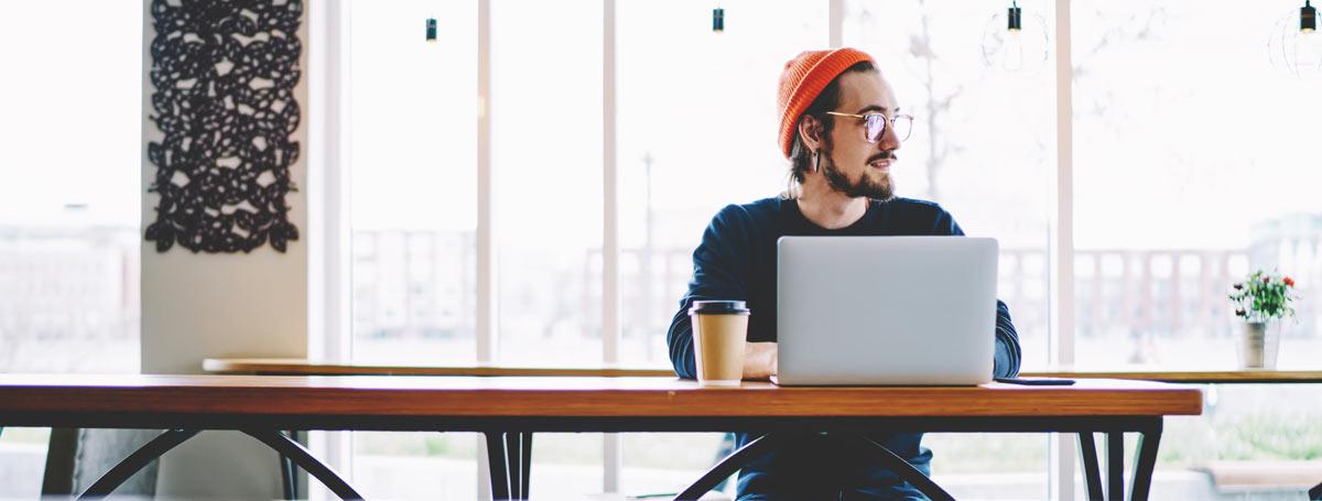 copywriter sitting at a café, writing on laptop