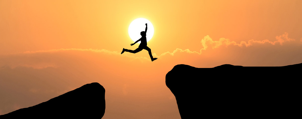 silhouette of man jumping over canyon in sunset