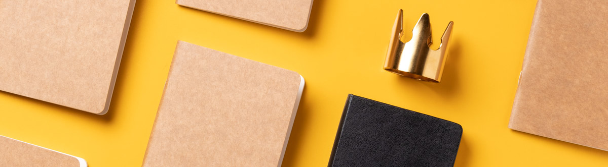 group of notebooks and a gold crown