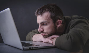 sad man looking at computer