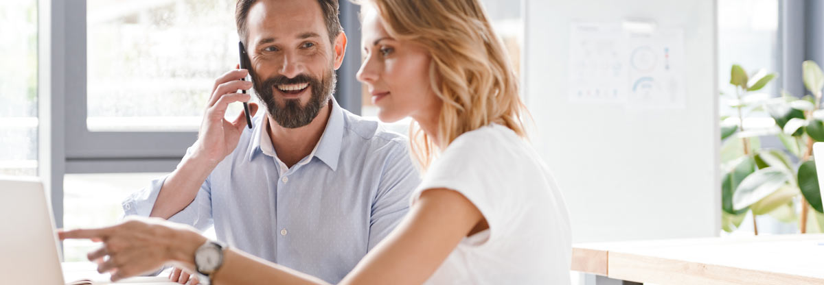 man smiling on phone with woman pointing at computer