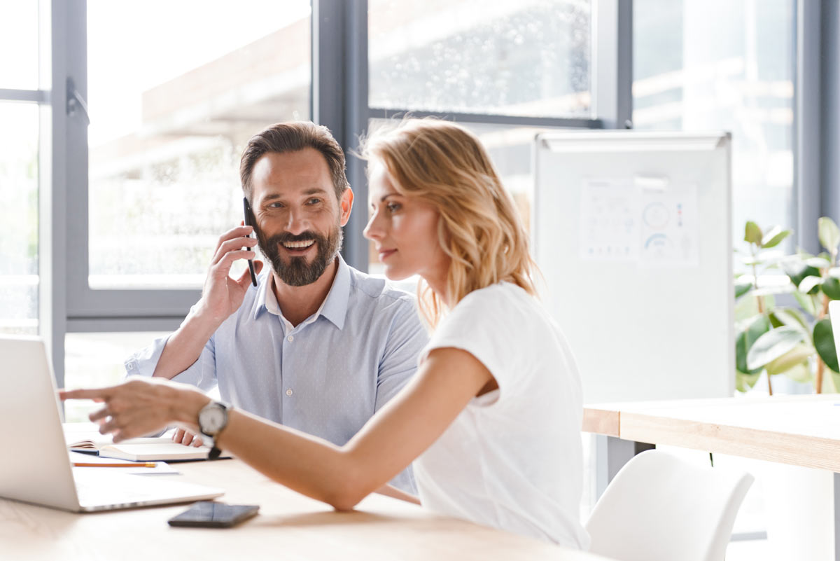 woman looking at a computer while man talks on a phone