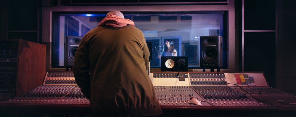 music engineer mixing at board while vocalist sings in isolation booth