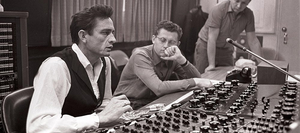 Johnny Cash sitting behind mixing board at Sun Studios