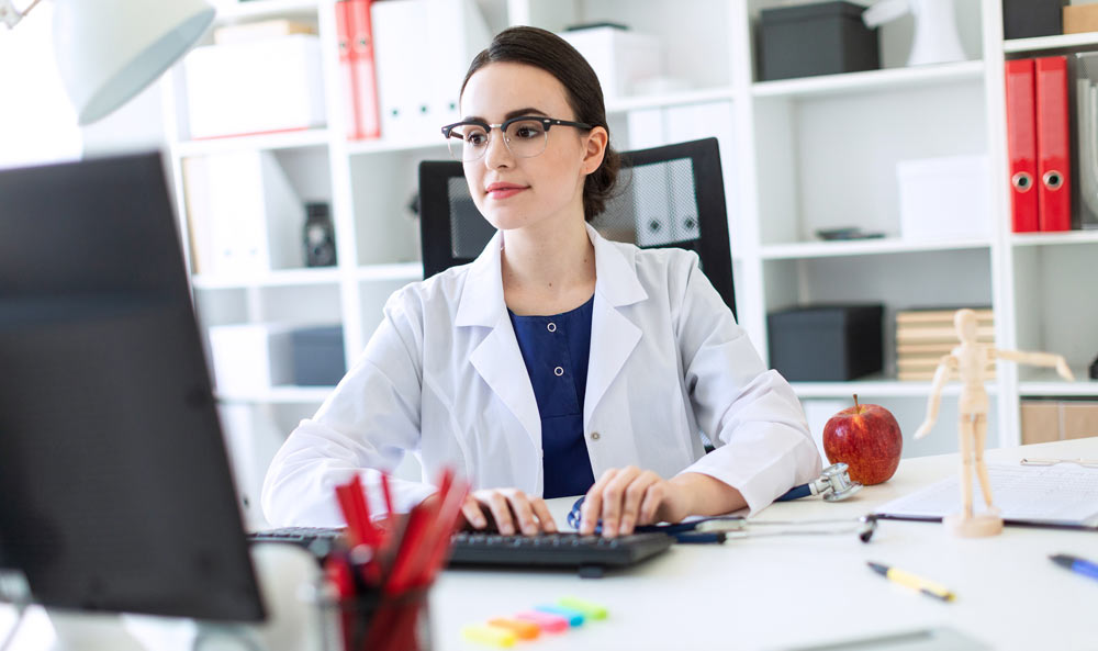 female dentist sitting behind a computer typing